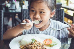 child eating Thai food